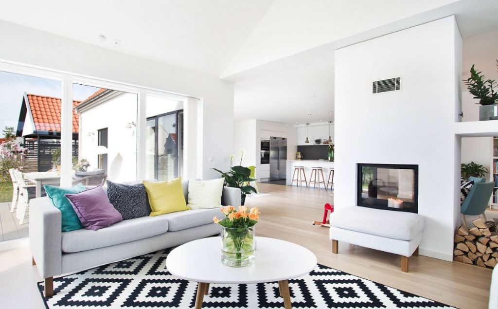 SPRAYDEC Open plan lounge/kitchen/diner with white walls, black and white geometric rug and colourful cushions